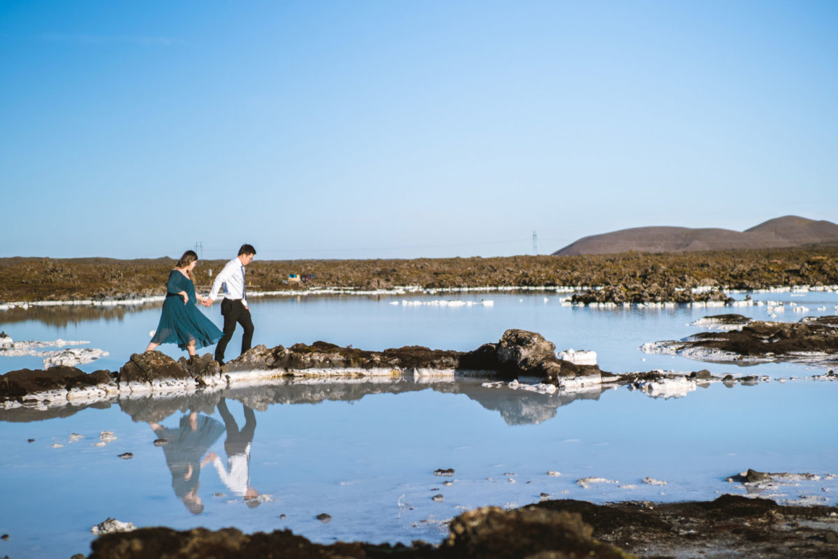Boy leading his girlfriend on the rocks in Blue Lagoon, Iceland.