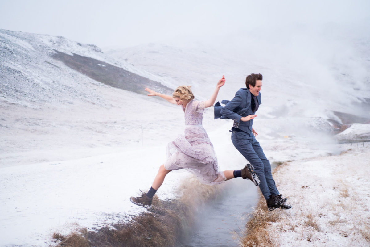 Bride and groom jumping across the river in ICeland