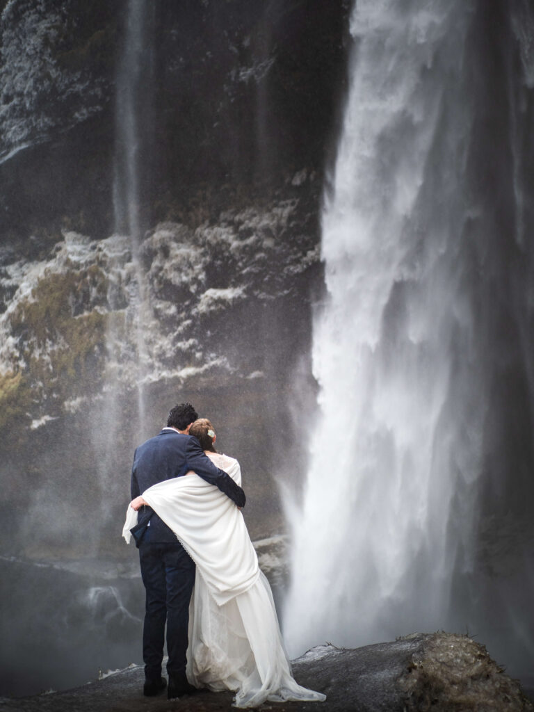 bride and groom cuddling in front of seljalandsfoss waerfall in inceland during the winter