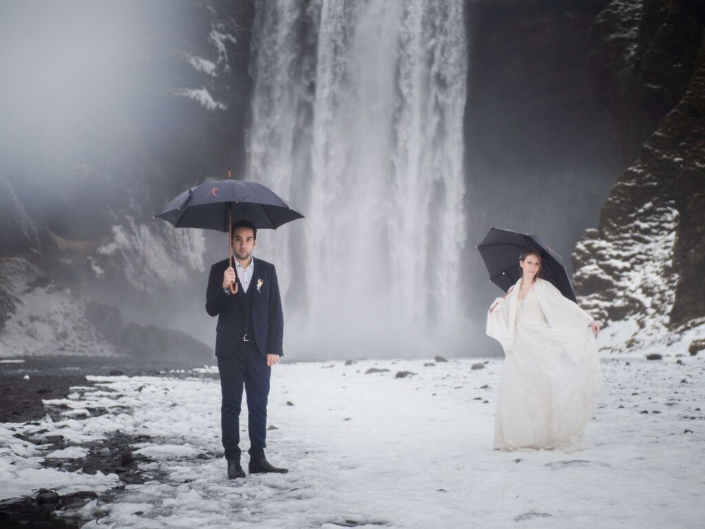 bride and groom with umbreallas by the waterfall in iceland