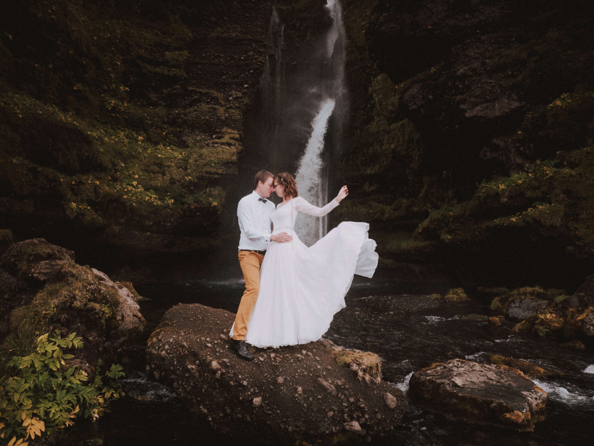 Bride and groom posin in Iceland with waterfall